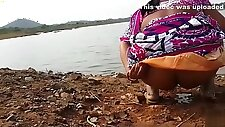 Indian woman peeing in the dirt by a lake